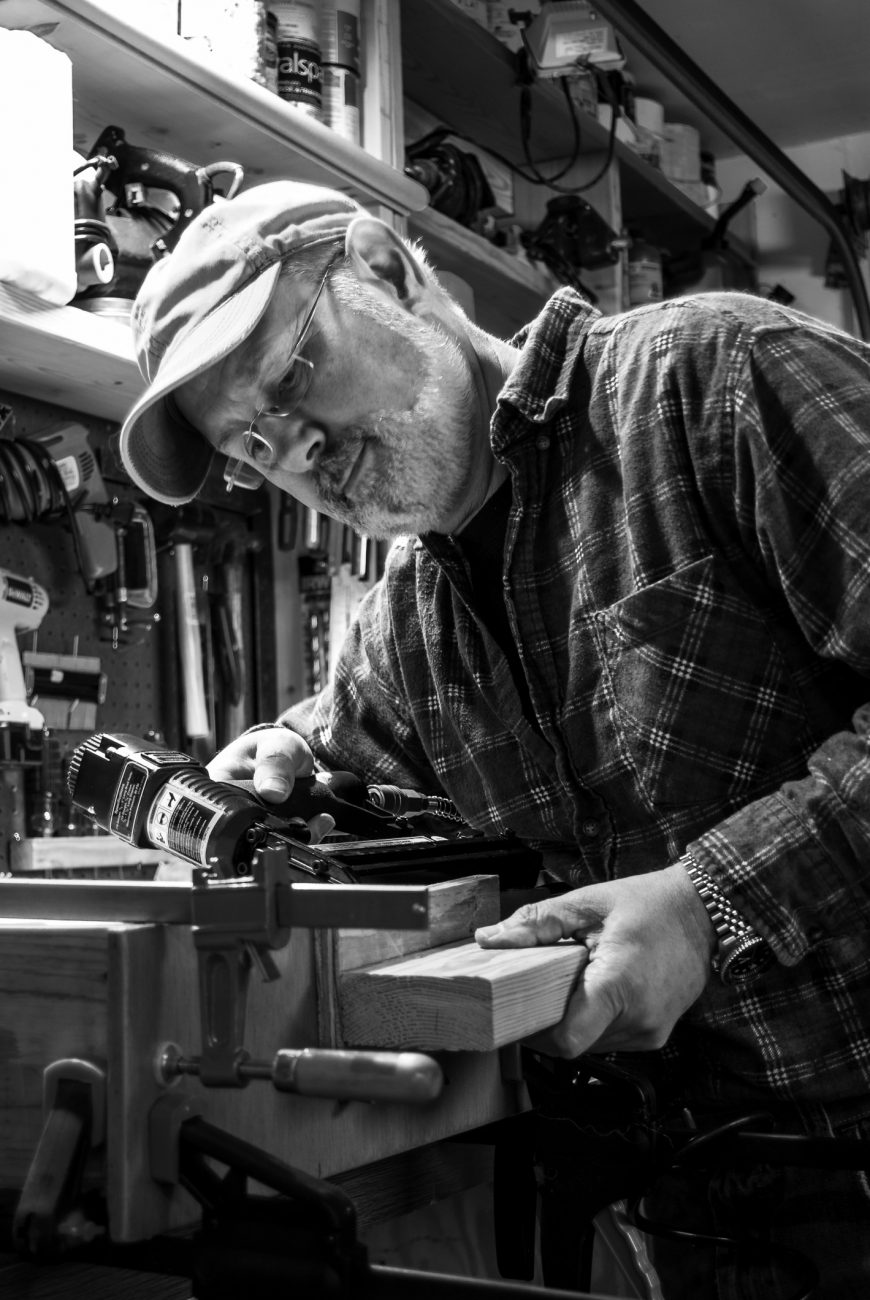 Black and white photograph of Gary Allman using a nail gun to rpair a kitchen drawer.