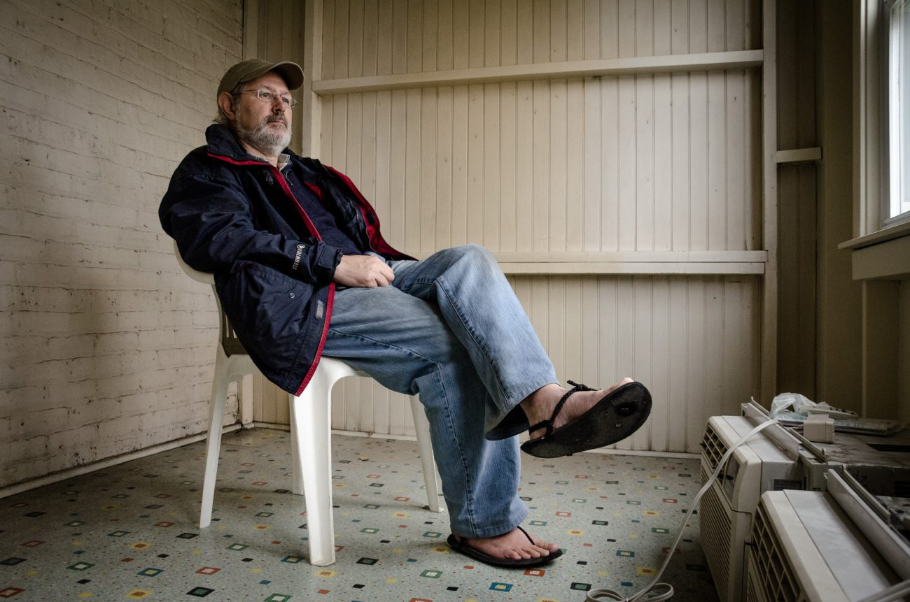 Gary Allman sitting in a plastic garden chair waiting for the trash man to arrive. Color photograph.
