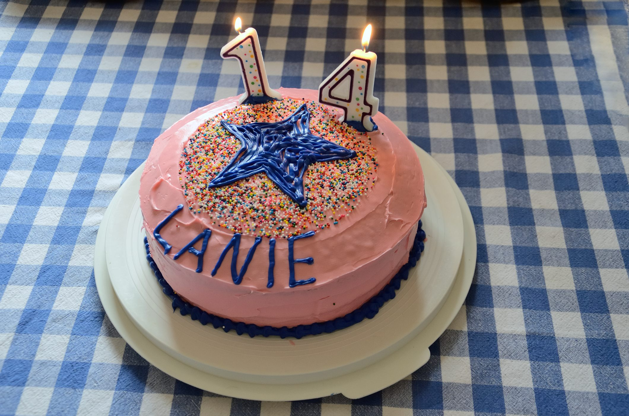 A pink iced birthday cake topped with a blue star pattern