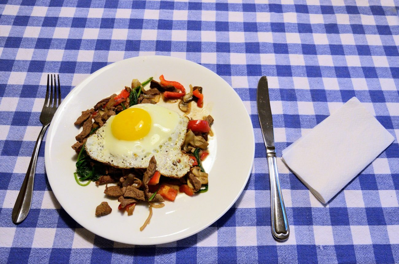 Breakfast meal - steak, mushrooms, vegitables topped off with an egg, sunny side up.