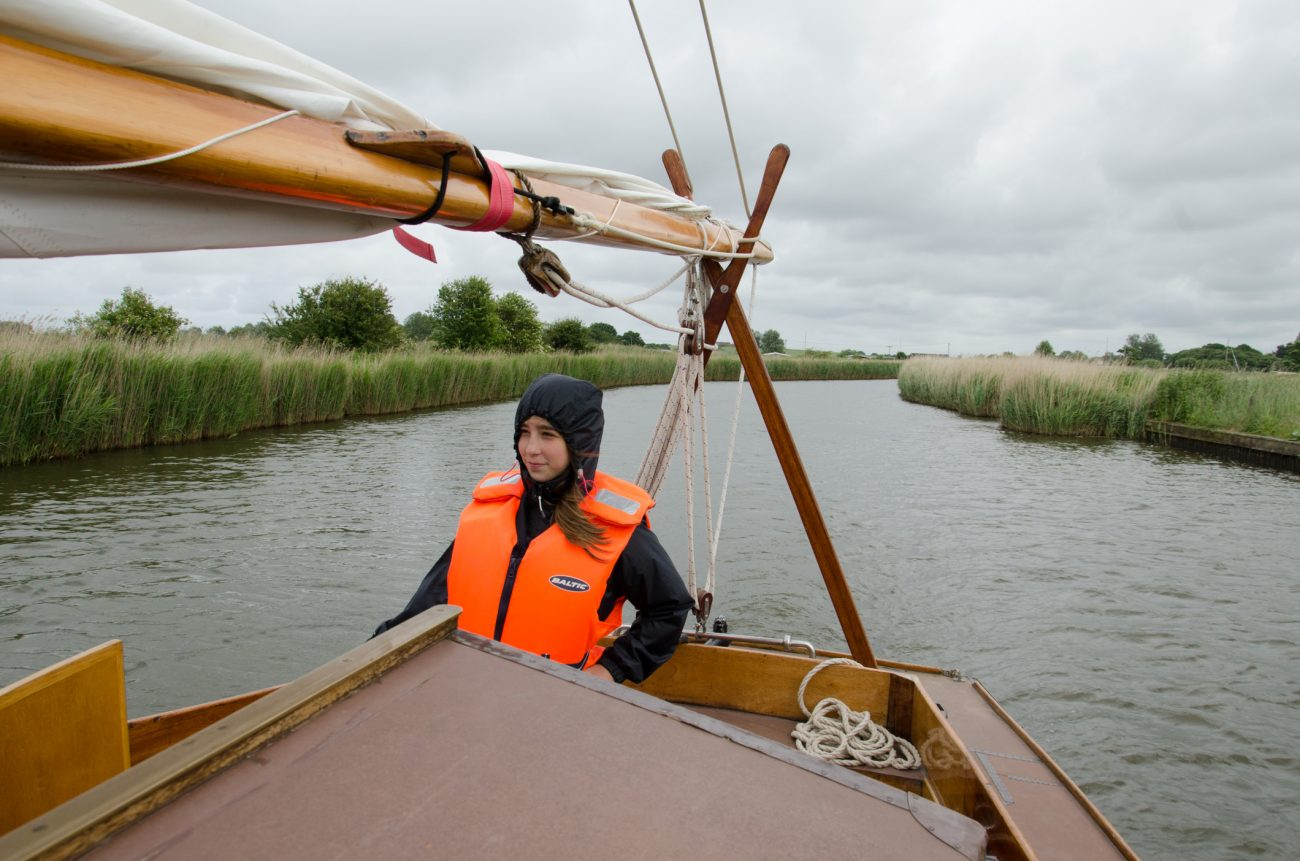 Lanie steering our sailboat on the Norfolk Broads