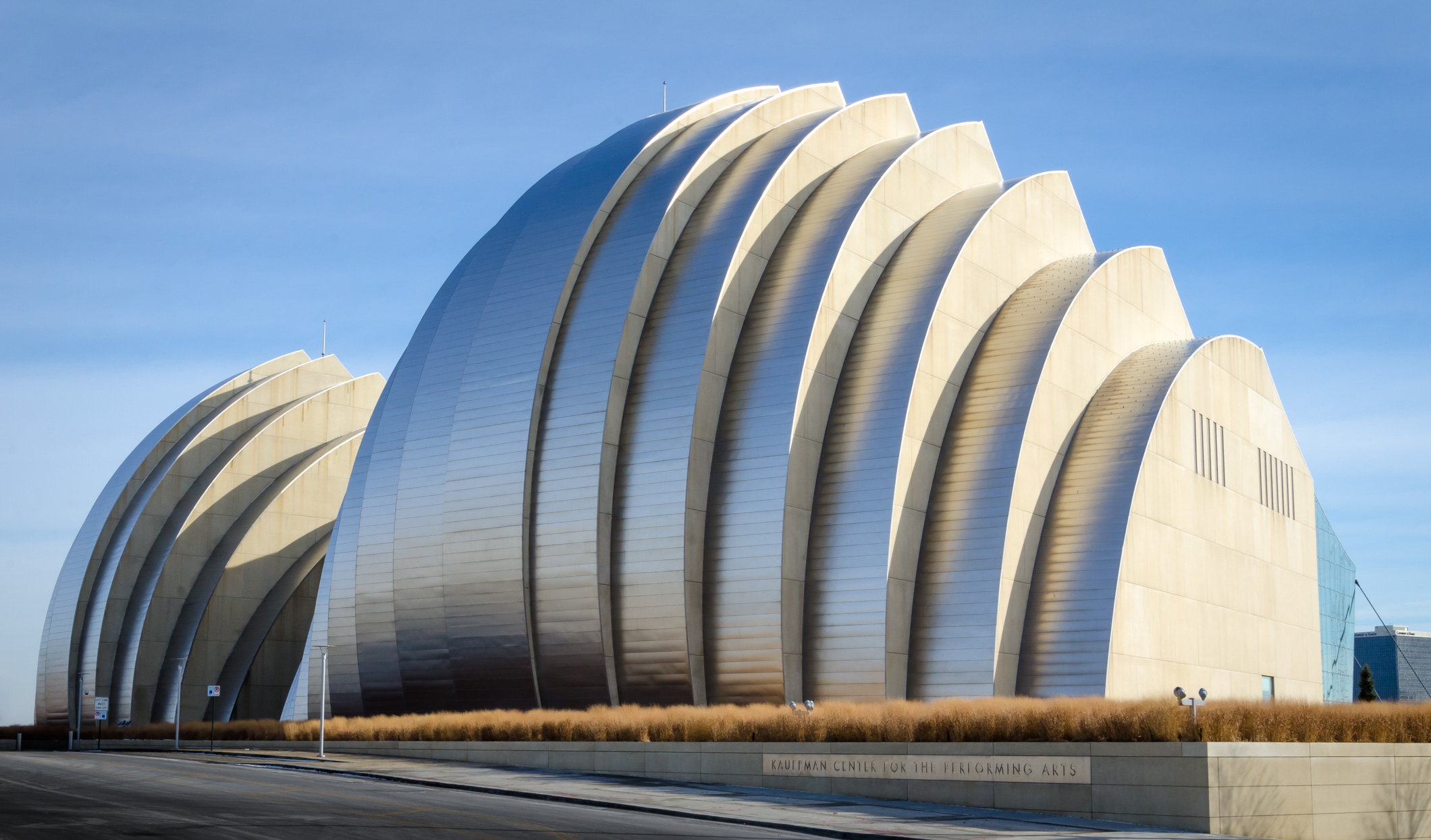 Color photograph of the Kauffman Center For The Performing Arts, Kansas City. The picture shows the blue of the sky reflected in the metal sheathing and is complemented by a stip of yellow-brown grass around the base.