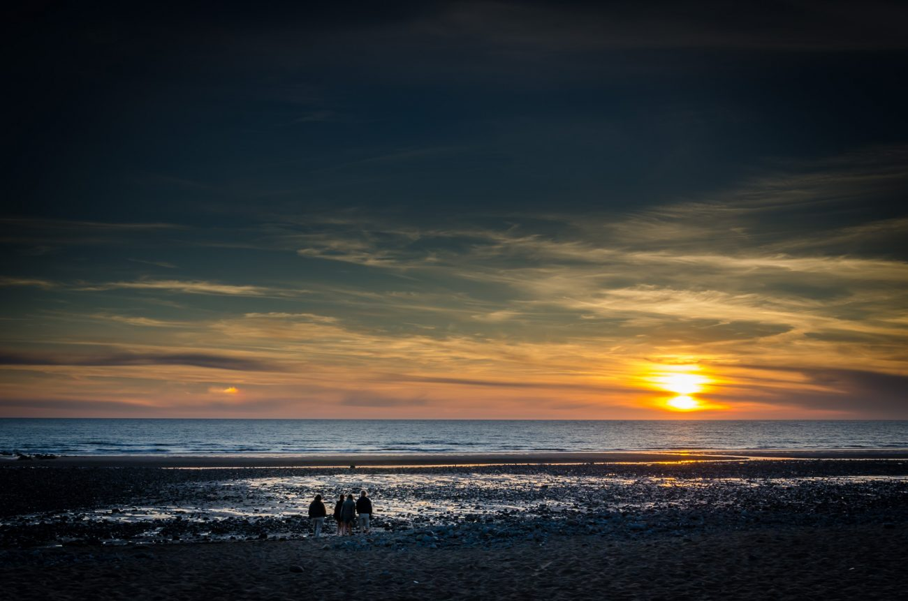 A group of people walk towards the sunset and sea on the beach at Widemouth, Cornwall, UK. Taken on June 24, 2014