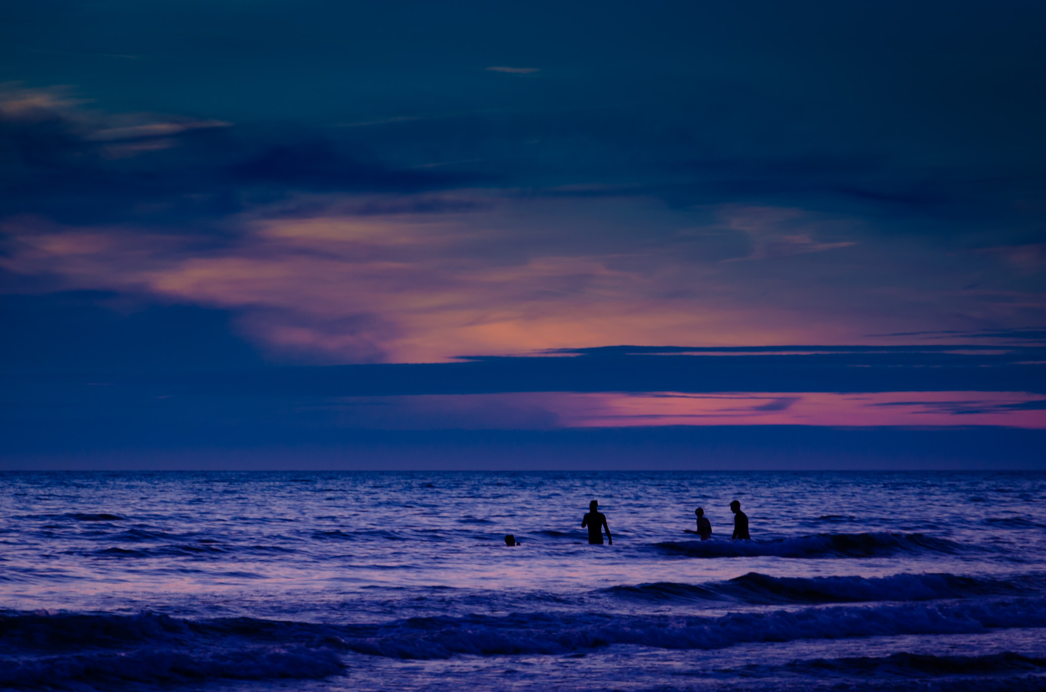 Silhouette of swimmers in the sea at sunset taken at Widemouth Bay Cornwall, UK on June 24, 2014.