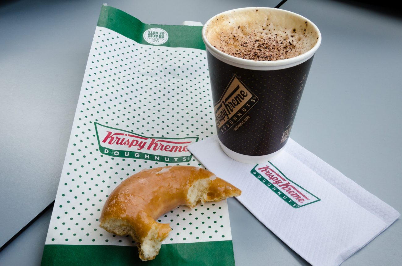 A photograph of a Krispy Kreme donut and a cup of coffee
