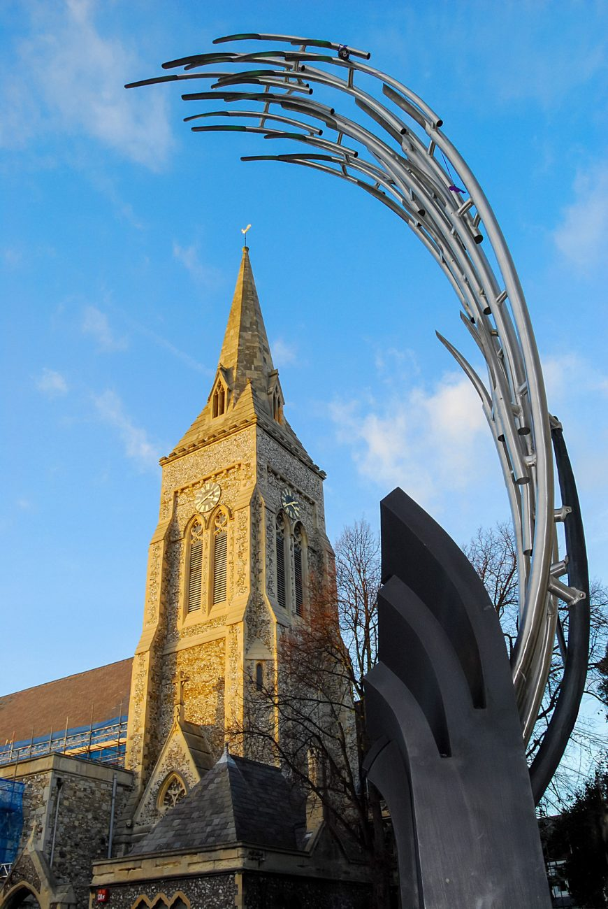 Photograph of St. Jude's Southsea frame by the modern 'wave' sculpture in the Palmerstone Road pedestrian precinct.