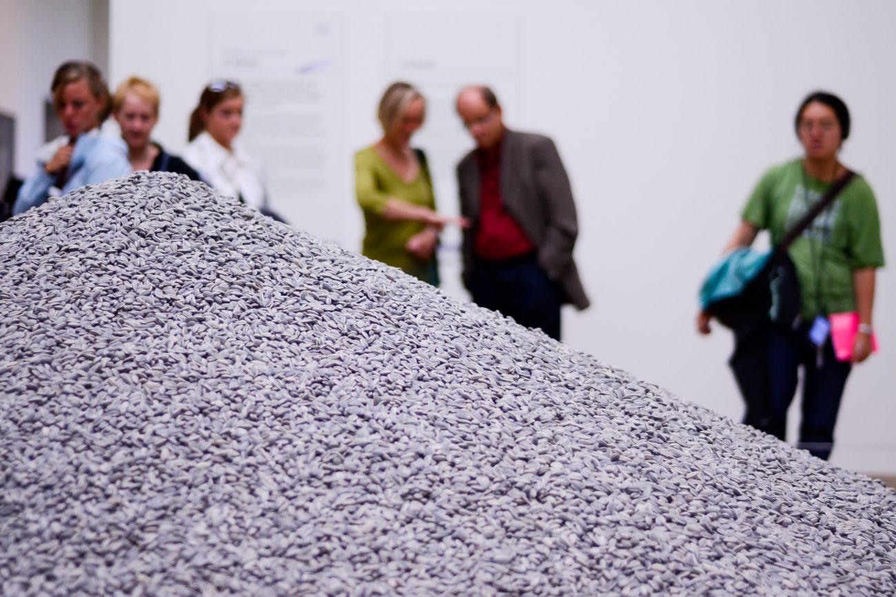 Visitors to the Tate Modern (London UK) study a huge pile of porcelain sunflower seeds