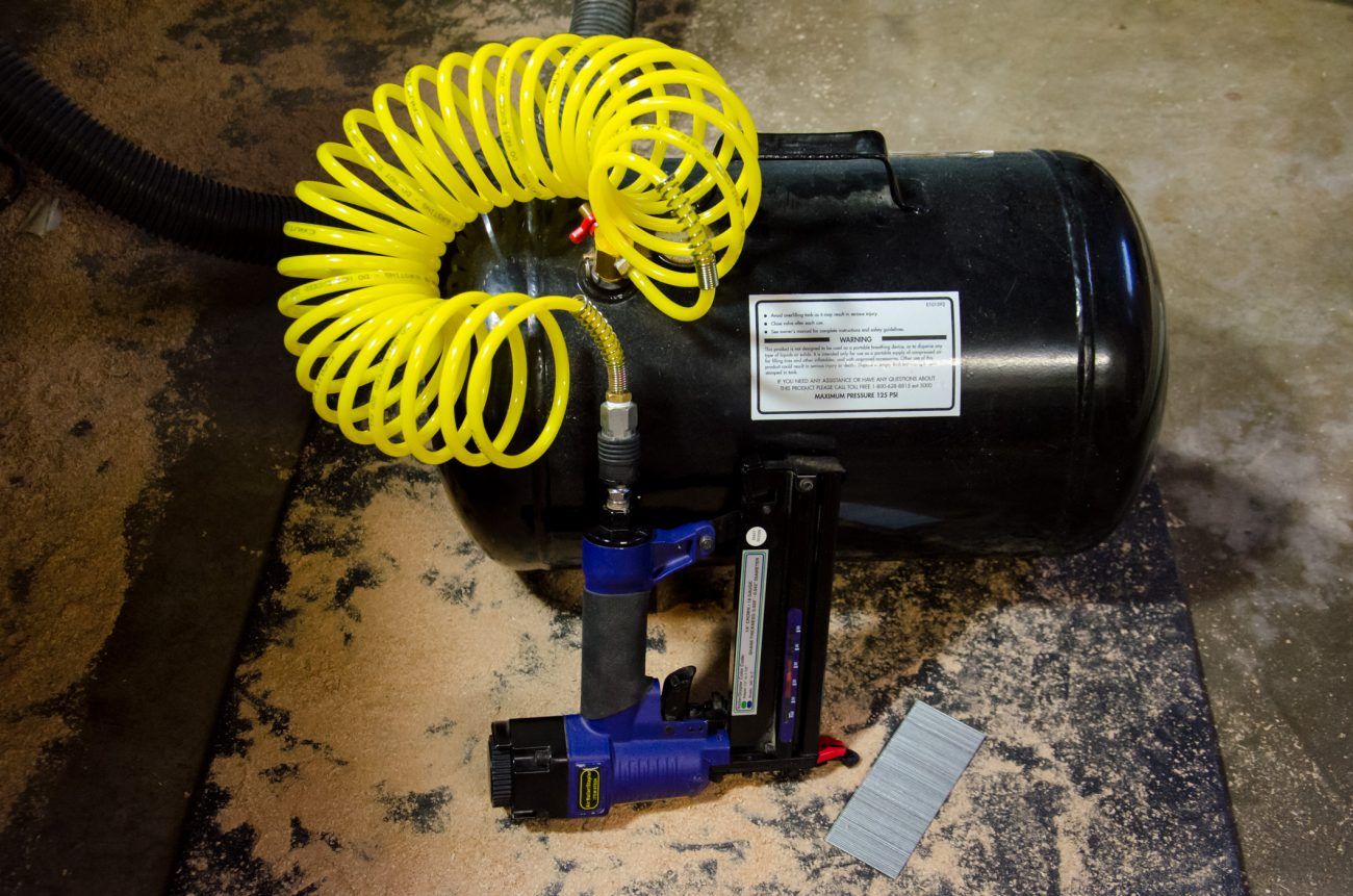 Photograph of a compressed air nail gun and eight gallon air storage tank