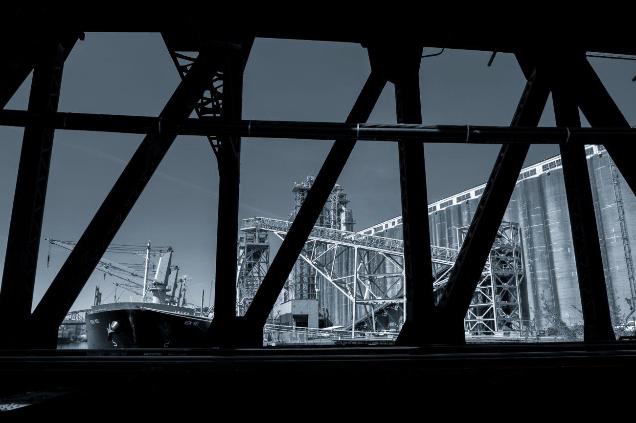 Black and White image. The motor vessel Ken Mei on the Willamette River, loading  grain near Steel Bridge, Portland Oregon.
