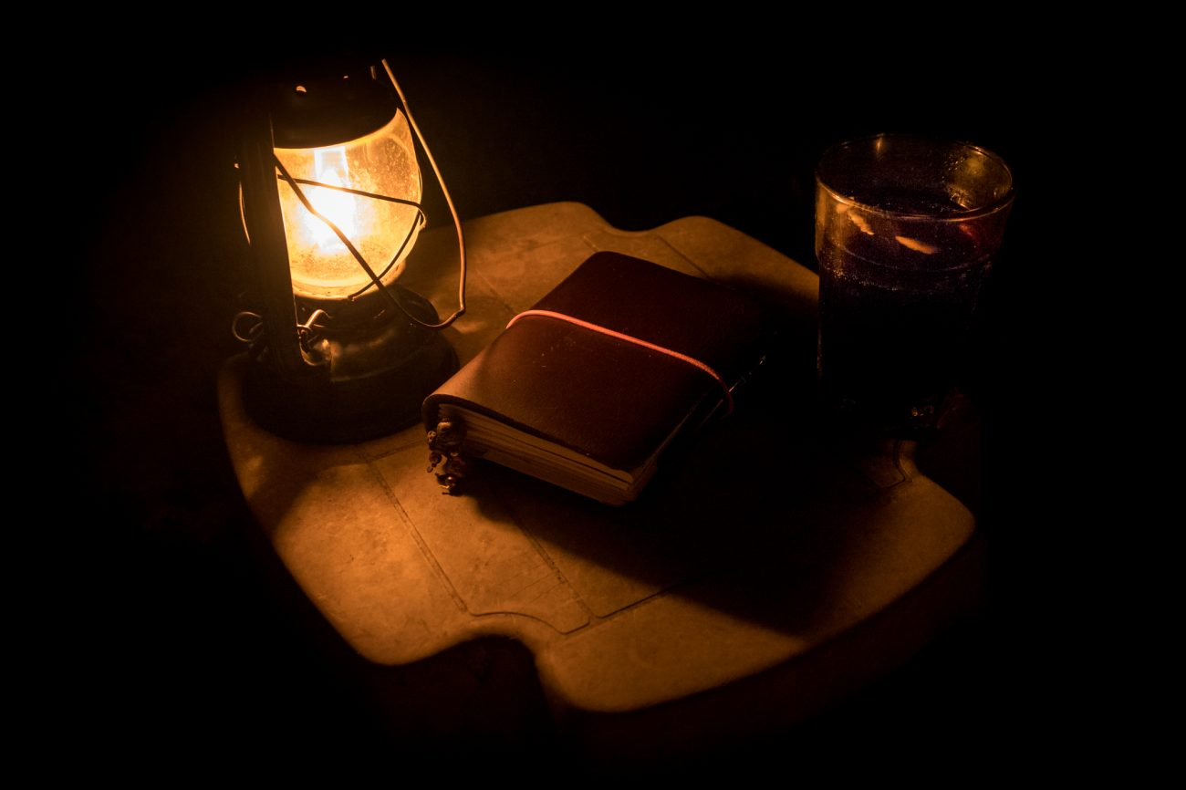 Color, night photograph of an oil lamp, leather bound journal and a cold drink