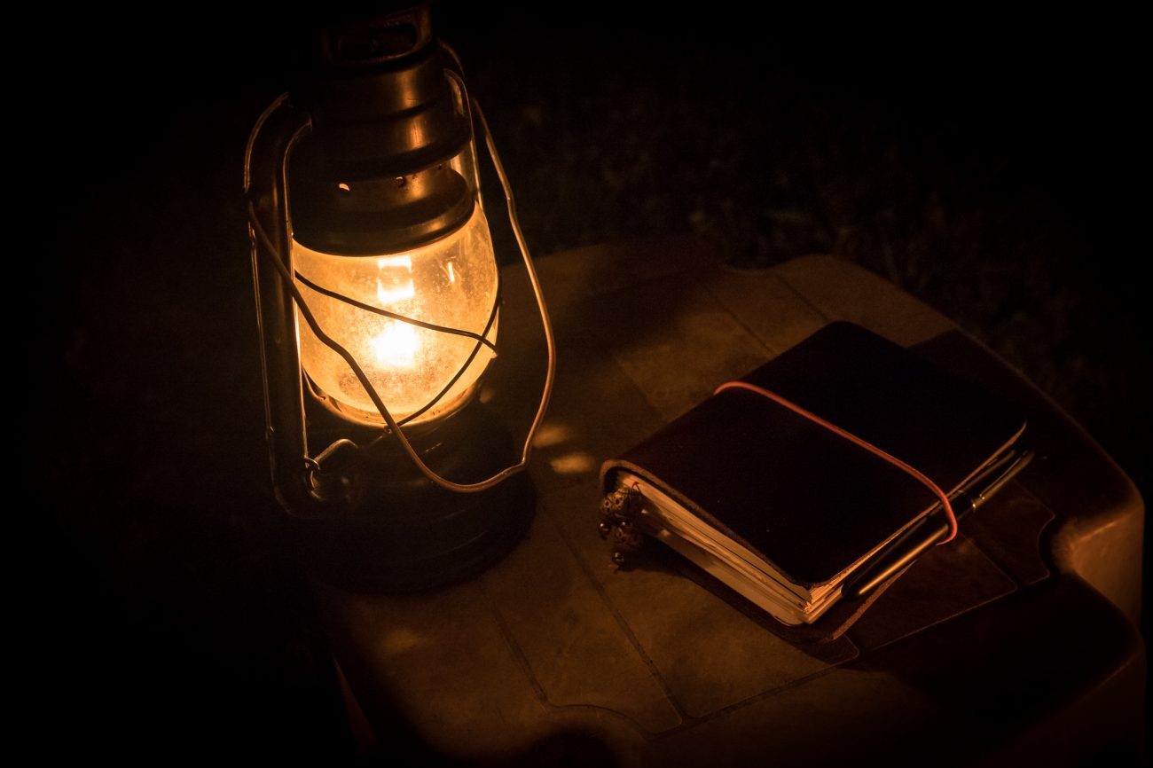 Color, night photograph of an oil lamp and leather bound journal