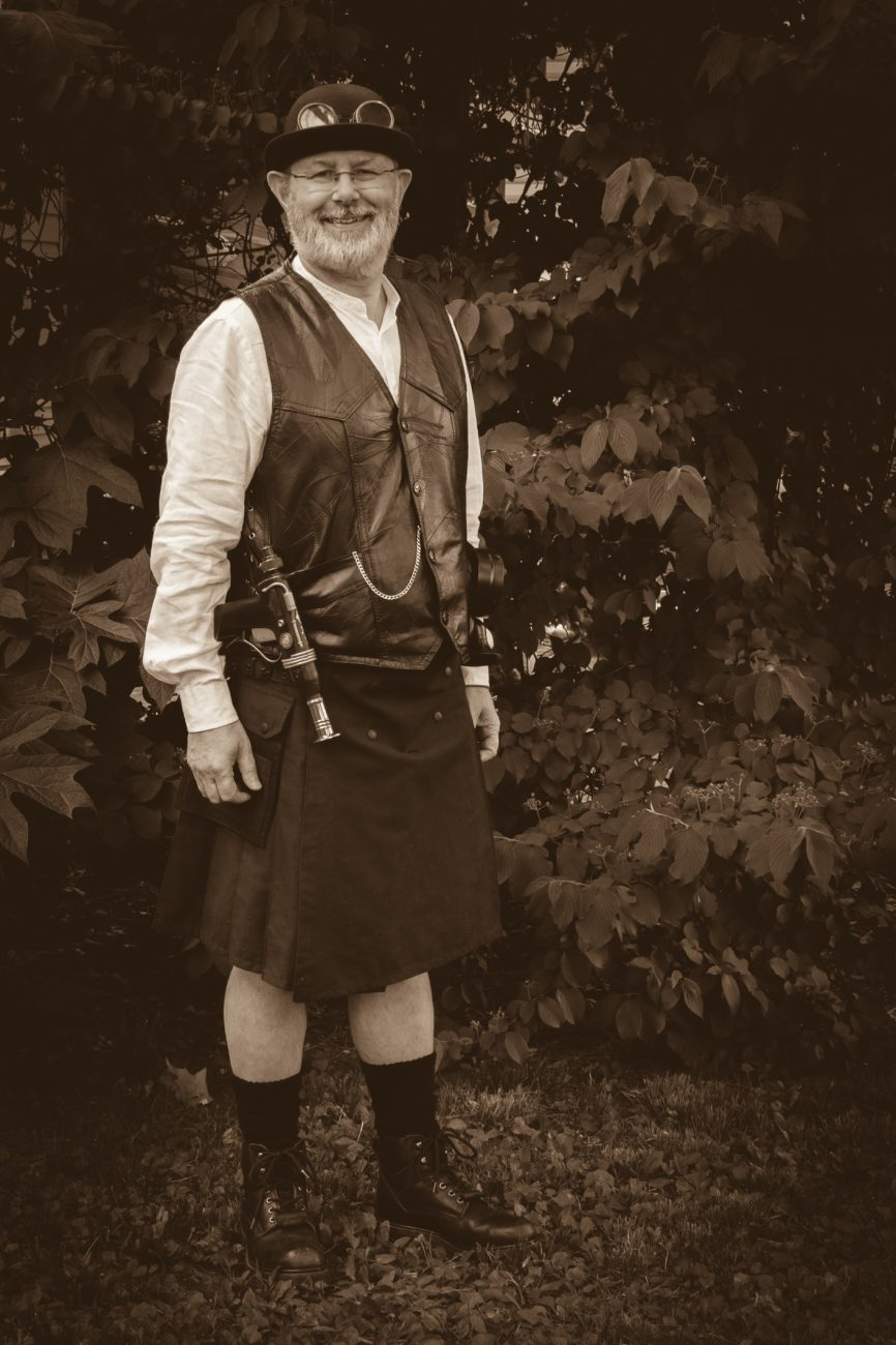Photograph of Gary Allman wearing a Steam Punk outfit featuring a utility kilt and leather vest
