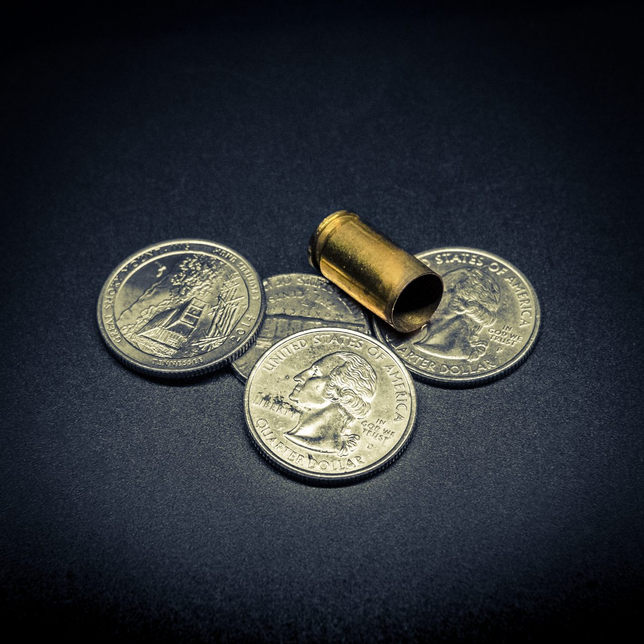 Duo-toned image of small change and a spent 9mm shell casing