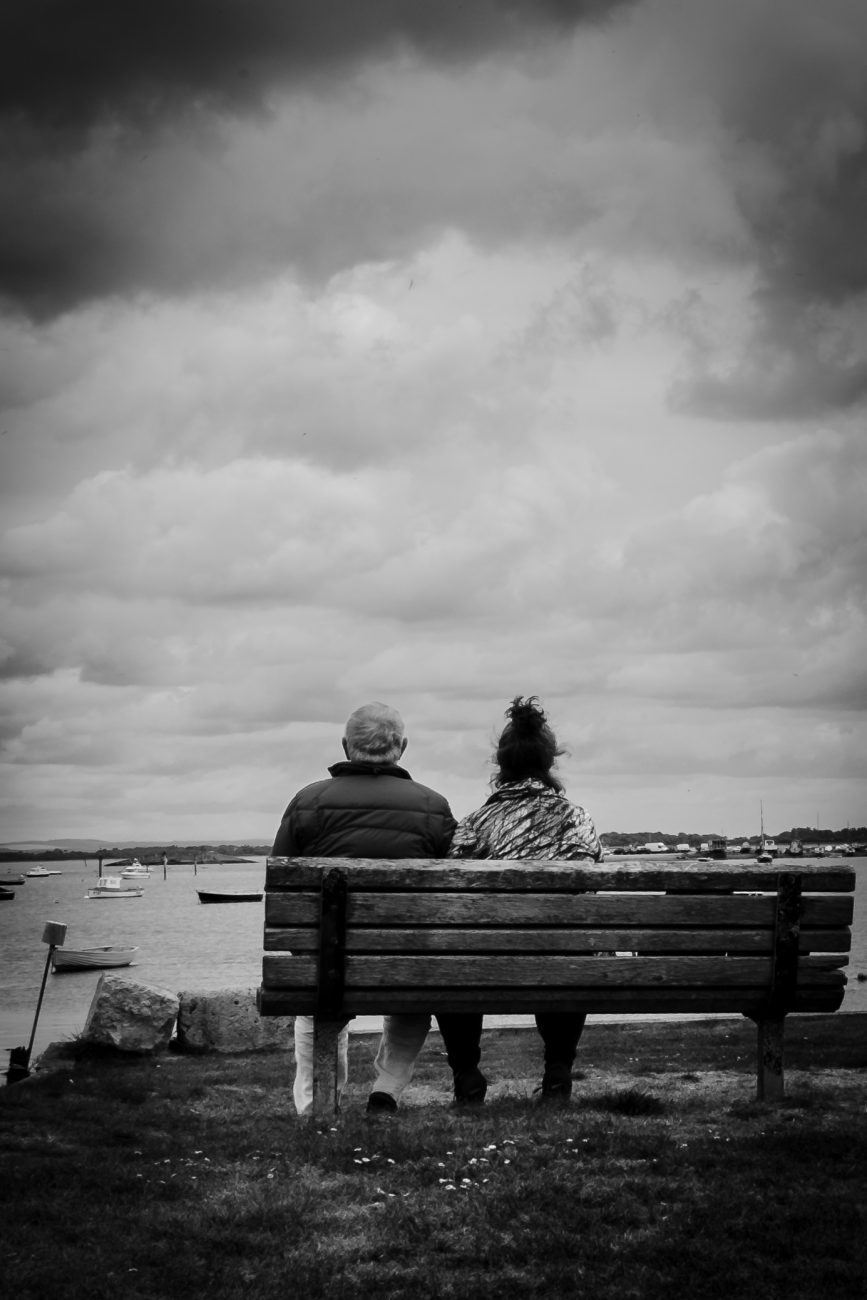 Black and White photograph of Gary Allman and Ginger Davis Allman sitting on a bench at Milton Locks, overlooking Langstone Harbour, Portsmouth, UK.