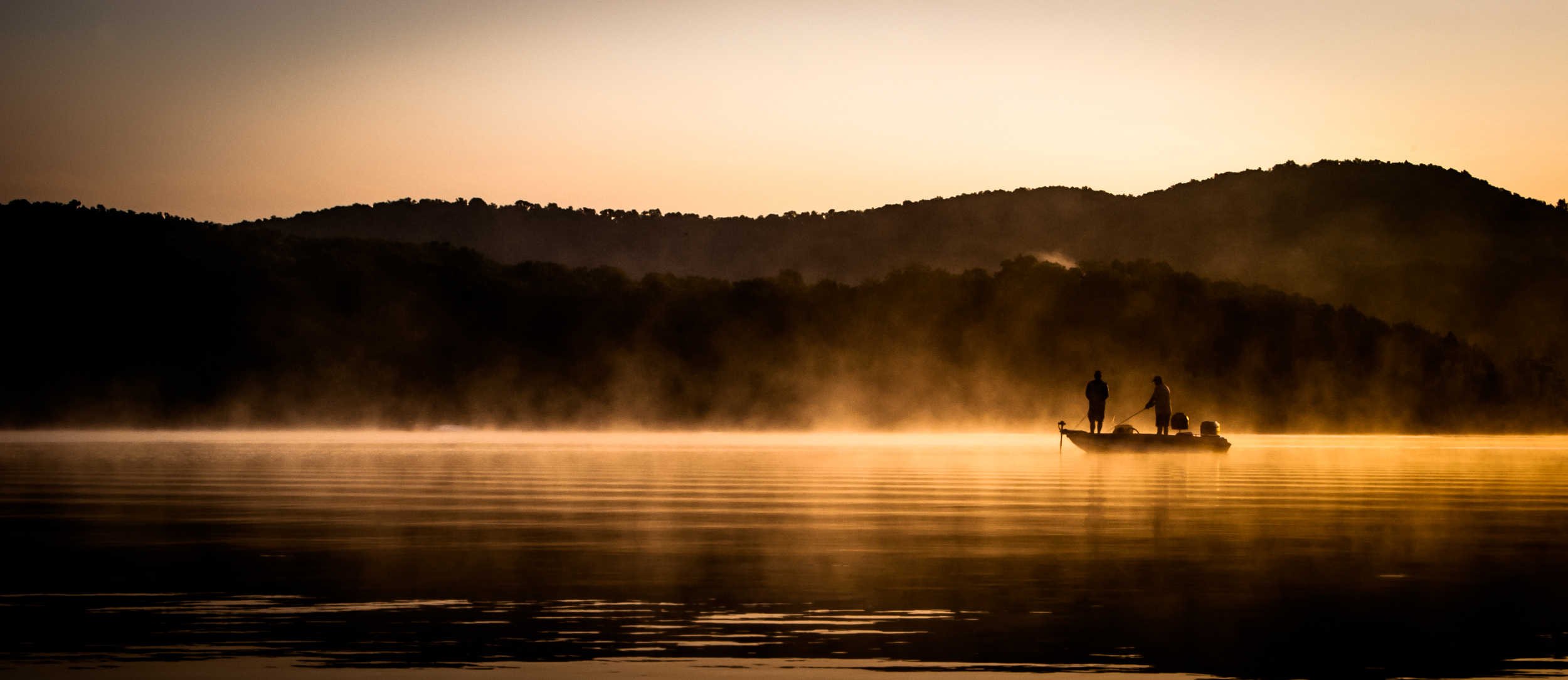 Photograph of two fishermen in a bass boat in silhouette at Sunrise on Table Rock Lake Missouri