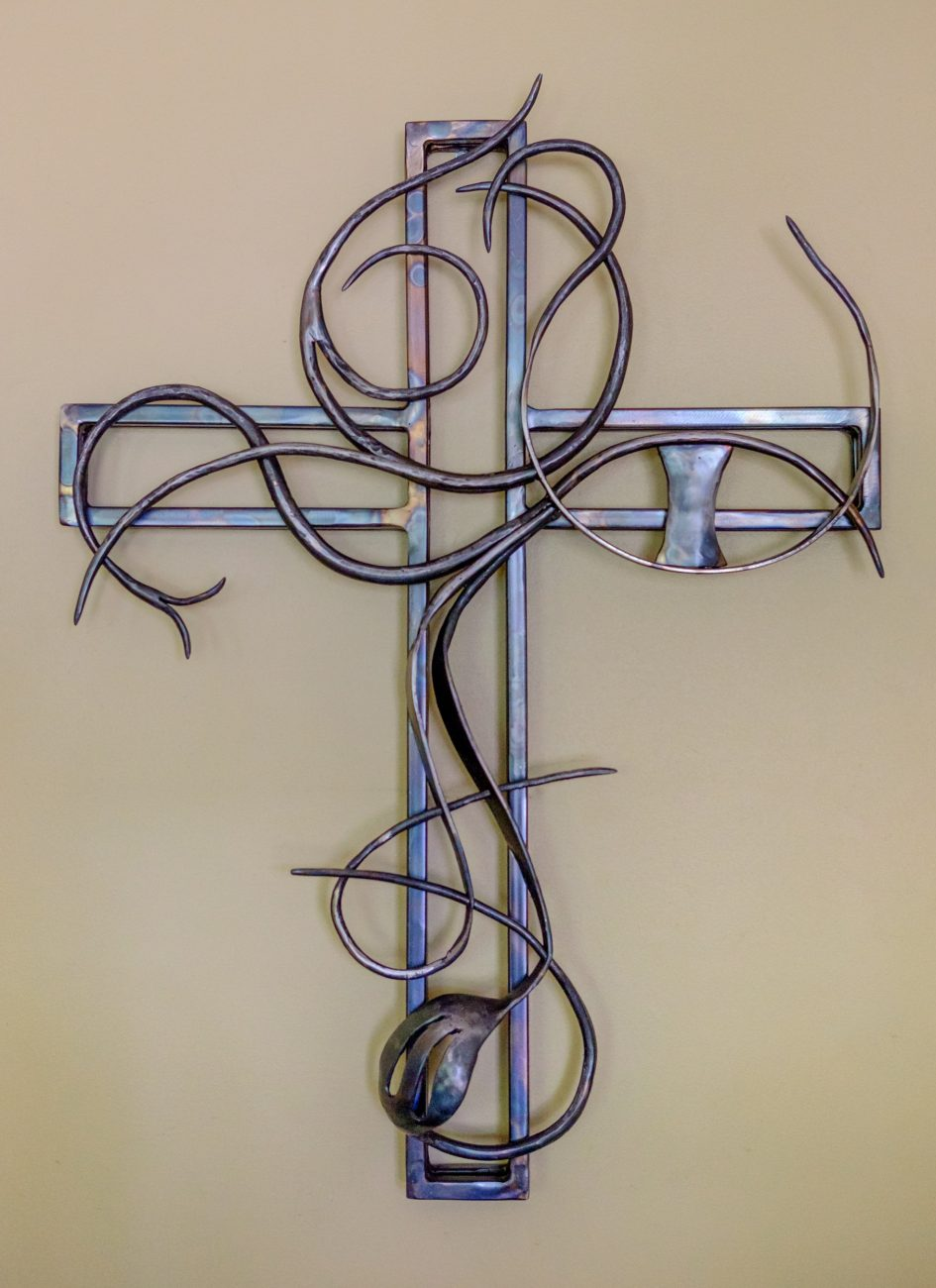 photograph of a welded metal cross outline with organic vines in mild steel
