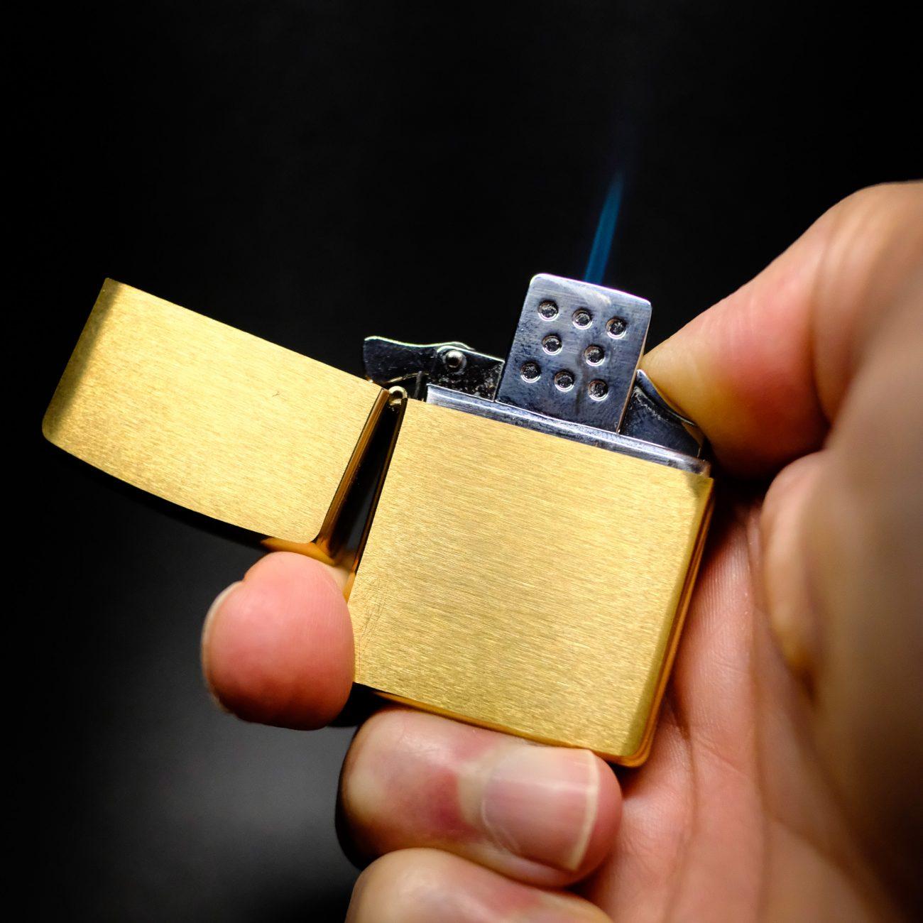 Photograph of a brass Zippo lighter with a butane insert