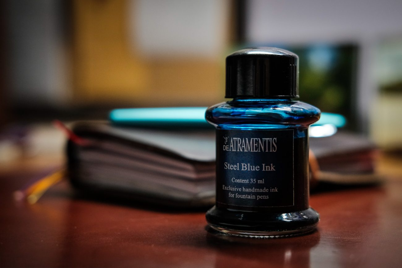 Color photograph of a bottle of DeAtramentis Steel Blue fountain pen ink