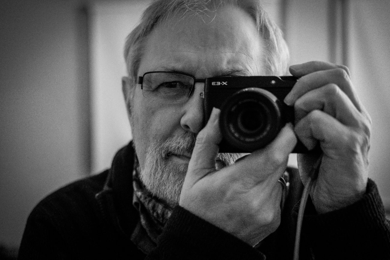Black and white photograph of Gary Allman posing with a Fujifilm X-E3 camera