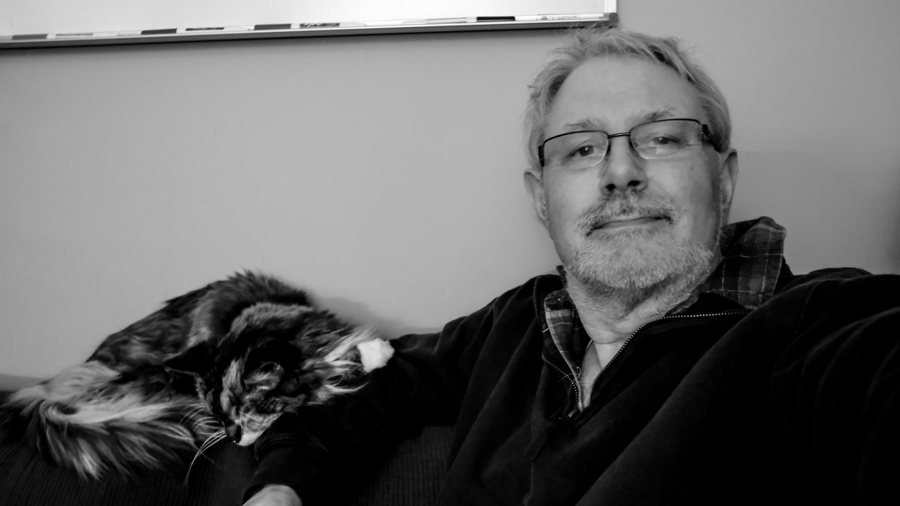 Black and white photograph of Gary Allman (Springfield Missouri) with Sprinky, a Maine Coon cat
