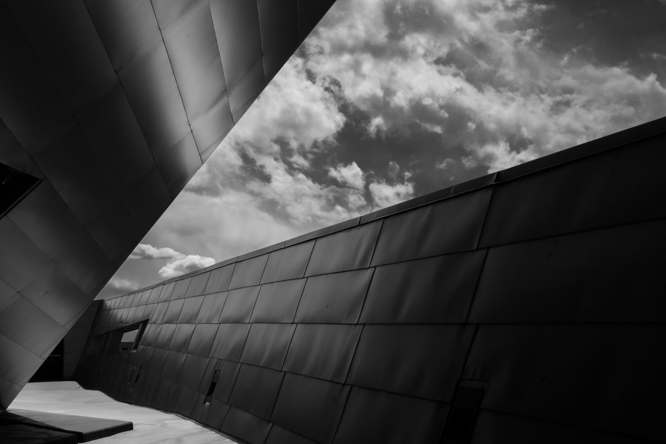 Black and white image of the sky and the titanium cladding of the Denver Art Museum - Frederic C. Hamilton Building. Architect: Daniel Libeskind