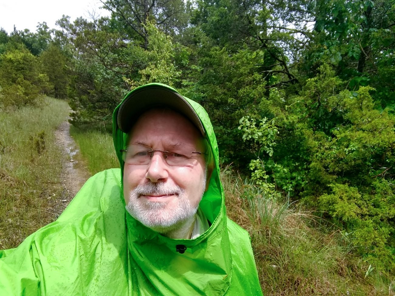 Gary Allman wearing a lime green rain poncho at Hercules Glades Wilderness.