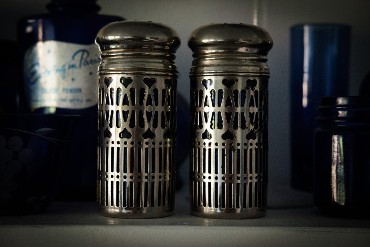 Photograph of ornate metal shrouded, blue glass salt and pepper shakers.