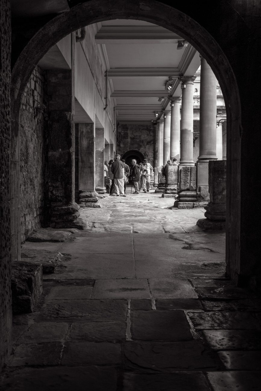 Black and white picture showing tourists at the Roman Baths in Bath UK.
