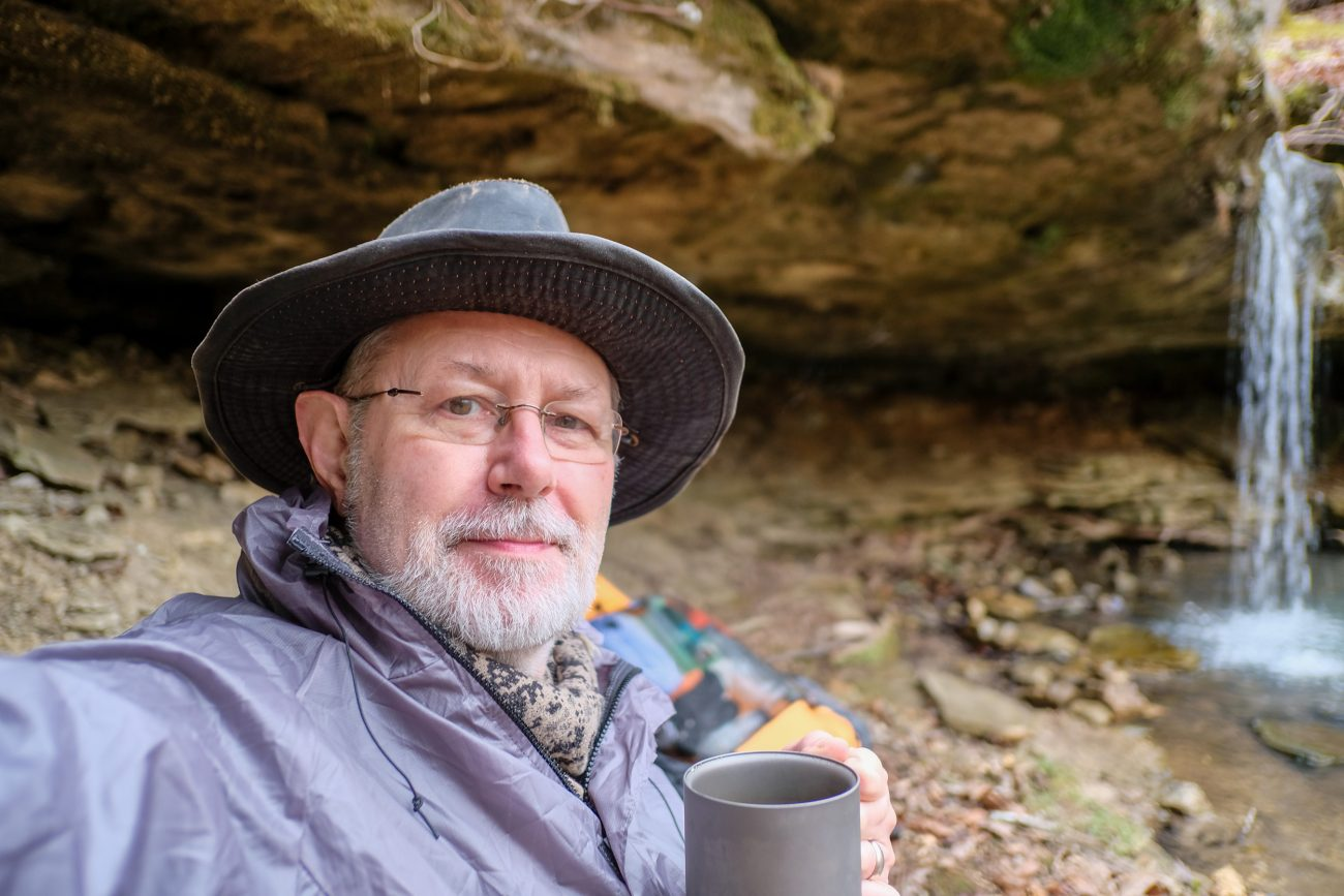 Photograph of Gary Allman drinking a cup of tea by some small falls on the Big Piney Trail, Paddy Creek Wilderness. November 2020.