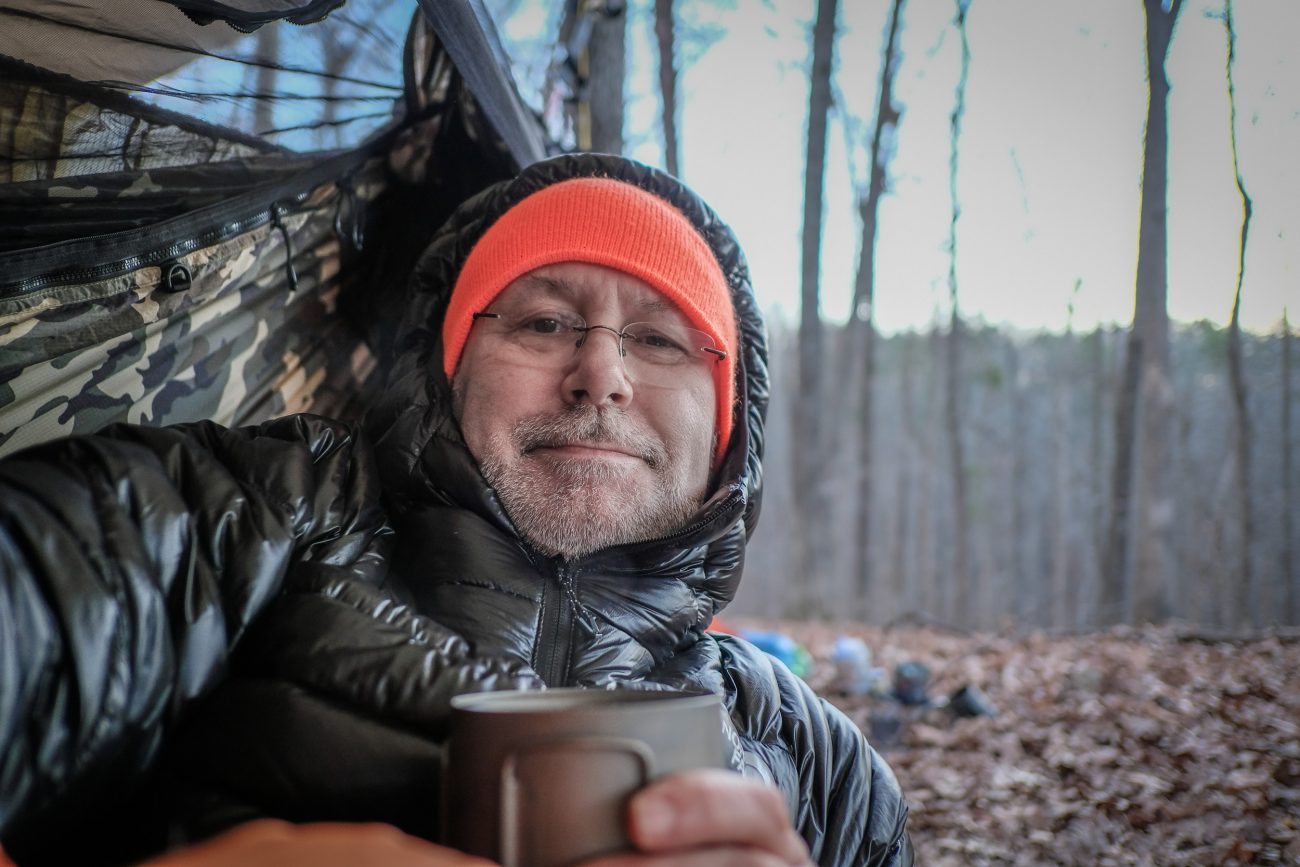 Photograph of Gary Allman with his morning tea in a hammock on the Berryman Trail, Missouri.