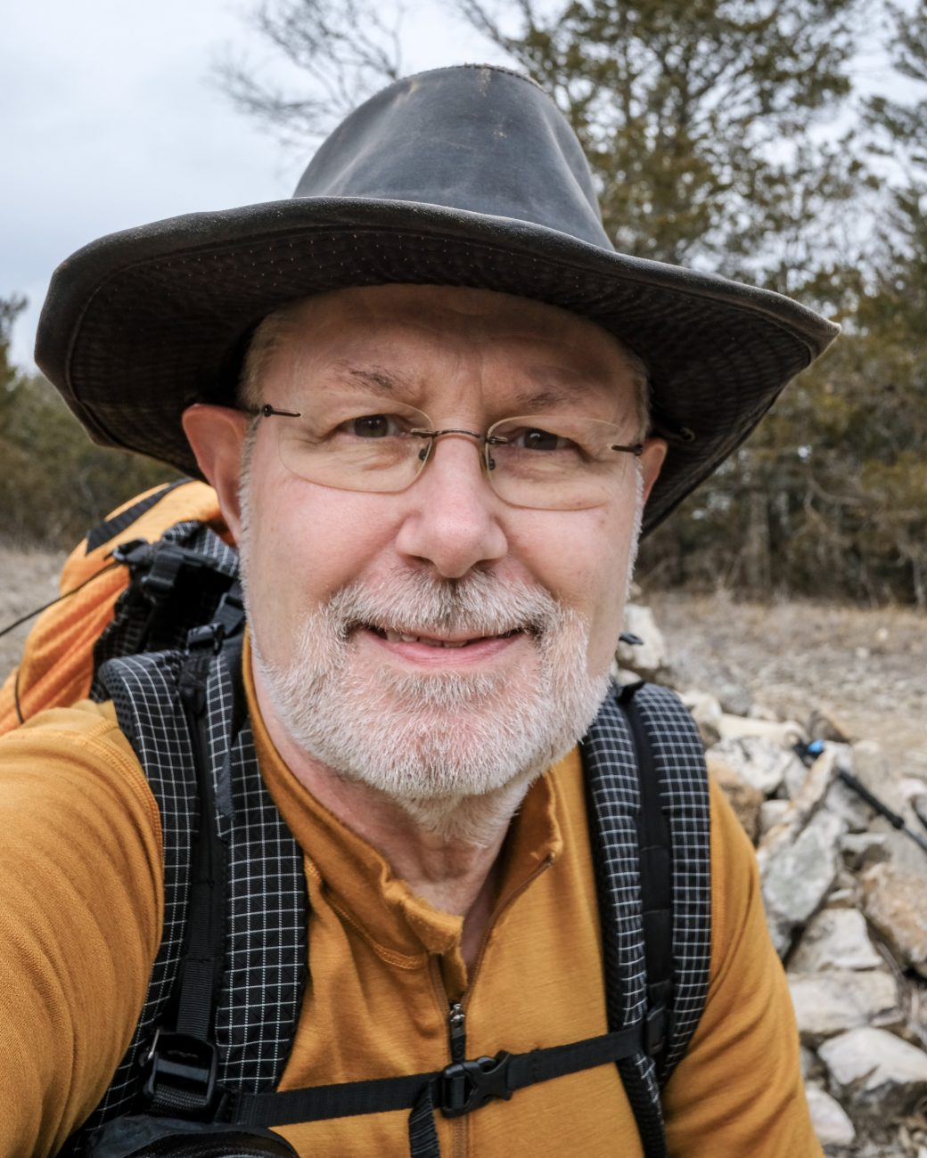 Photograph of Gary Allman in front of the Pole (Pete) Hollow Trail cairn, Hercules Glades Wilderness, Missouri. February 2021.
